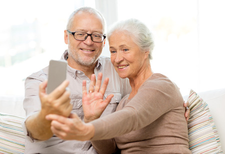 self communication: family, technology, age, gesture and people concept - happy senior couple with smartphone making selfie and waving hand at home