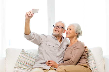 family, technology, age and people concept - happy senior\ couple with smartphone making selfie at home