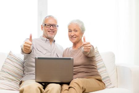 가족, 기술, 제스처, 연령 및 사람들이 개념 - 집에서 엄지 손가락을 보여주는 노트북 컴퓨터와 함께 행복 한 고위 커플 스톡 콘텐츠
