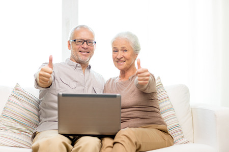 familie, technologie, gebaar, leeftijd en mensen concept - gelukkig senior paar met laptop computer zien thumbs up thuis Stockfoto