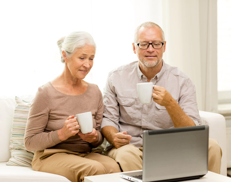 family, technology, drinks, age and people concept - happy senior couple with laptop computer and cups at home photo