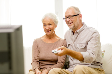 family, technology, age and people concept - happy senior couple watching tv at home photo