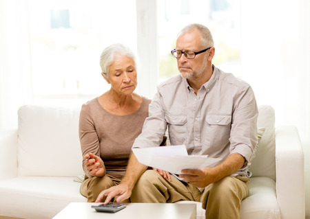 business savings: family, business, savings, age and people concept - smiling senior couple with papers and calculator at home Stock Photo