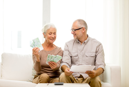 business savings: family, business, savings, age and people concept - smiling senior couple with papers, money and calculator at home