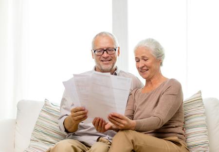 vejez feliz: familia, los negocios, la edad y el concepto de la gente - feliz pareja de alto nivel con los papeles en el hogar