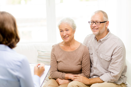 famille, les relations, l'âge et personnage - couple de personnes âgées heureux et psychologue ou un travailleur social à la maison