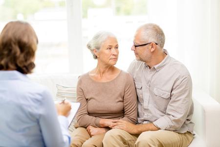 家族、関係、年齢および人々 のコンセプト - 年配のカップルと心理学者や家庭でのソーシャル ワーカー