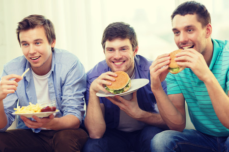 unhealthy living: friendship, food and leisure concept - smiling friends with soda and hamburgers at home