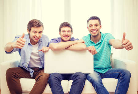 small group: friendship and advertising concept - smiling male friends holding white blank board and showing thumbs up