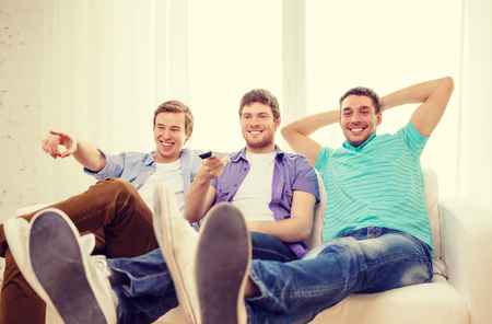 out of control: friendship, technology and home concept - smiling male friends with remote control at home Stock Photo