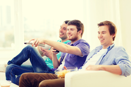 out of control: friendship, technology and home concept - smiling male friends with remote control and junk food at home