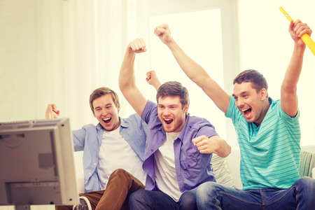 three friends: friendship, sports and entertainment concept - happy male friends with vuvuzela watching sports on tv