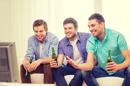 nonalcoholic beer: friendship, sports and entertainment concept - happy male friends with beer watching tv at home Stock Photo