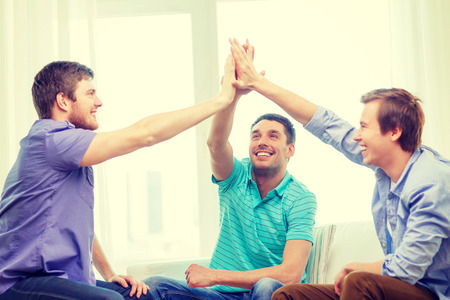 winner man: teamwork, friendship and happiness concept - smiling male friends giving high five at home Stock Photo