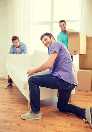 arrive: moving, real estate and friendship concept - smiling male friends with sofa and boxes at new home