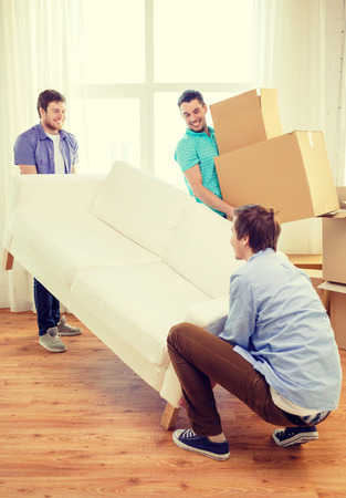 moving, real estate and friendship concept - smiling male friends with sofa and boxes at new home Reklamní fotografie - 33043487