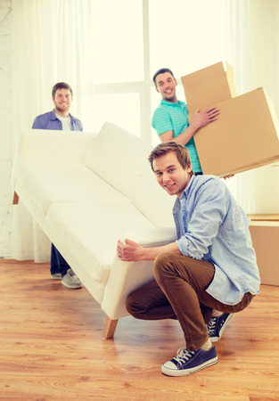 accommodation: moving, real estate and friendship concept - smiling male friends with sofa and boxes at new home