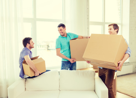 room mate: moving, real estate and friendship concept - smiling male friends carrying boxes at new place