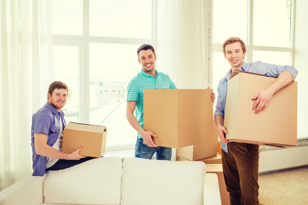 large group of items: moving, real estate and friendship concept - smiling male friends carrying boxes at new place