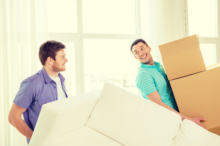 room mate: moving, real estate and friendship concept - smiling male friends with sofa and boxes at new home