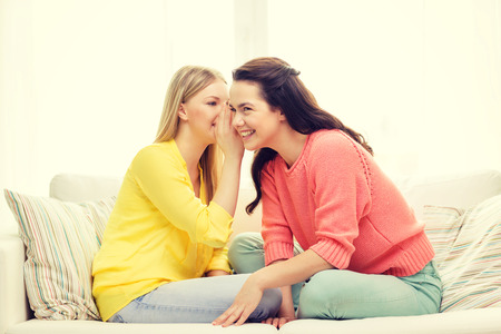 blab: friendship, gossip and happiness concept - one girl telling another secret Stock Photo