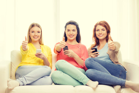 friendship, technology and internet concept - three smiling teenage girls with smartphones at home showing thumbs up photo