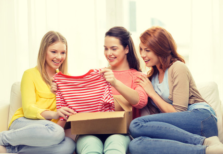 transportation, post and friendship concept - three smiling teenage girls opening cardboard box at home Banco de Imagens