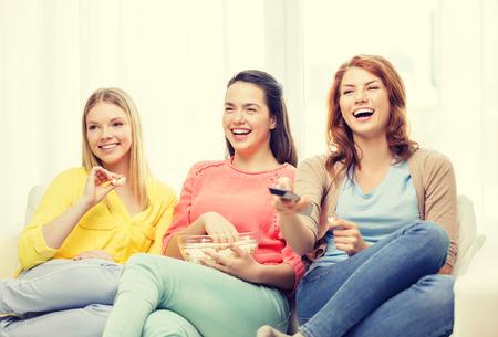 thuis, technologie en vriendschap concept - drie glimlachende tienermeisje op TV thuis en het eten van popcorn