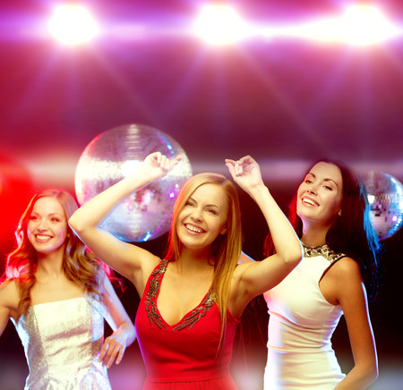 night out: new year celebration, friends, bachelorette party, birthday concept - three beautiful woman in evening dresses dancing in the club