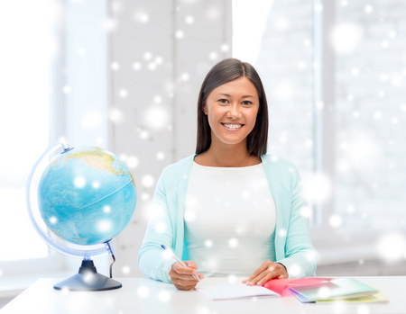 education, winter, technology and people concept - smiling young woman with globe and tablet pc computer indoors photo