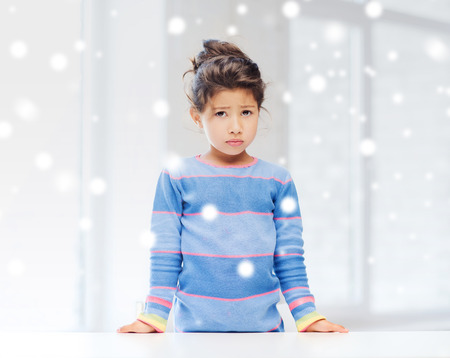 childhood, emotions and people concept - sad or tired little\ girl indoors