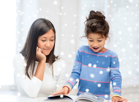 latin kids: childhood, education, family and people concept - smiling little girl and mother or teacher with book indoors