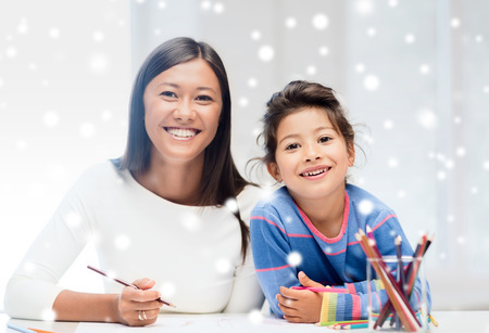 childhood, family, education and people concept - smiling little girl and mother or teacher drawing with coloring pencils indoors photo