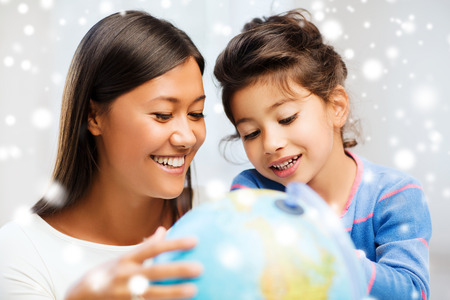 asian teacher: childhood, education, family and people concept - smiling little girl and mother or teacher with globe indoors