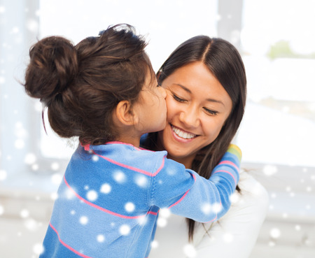 mother child: childhood, happiness, family and people concept - smiling little girl and mother hugging indoors