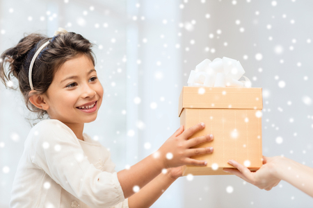 grateful: holidays, christmas, childhood and people concept - smiling little girl with gift box at home Stock Photo