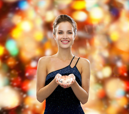 people, christmas, winter holidays and glamour concept - smiling woman in evening dress with diamond over red lights background photo