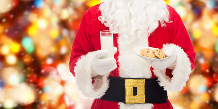 christmas drink: christmas, holidays, food, drink and people concept -close up of santa claus with glass of milk and cookies over red lights background