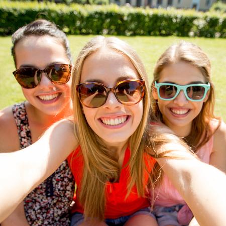 дружба, отдых, лето, технологии и люди концепции - группа улыбается девочек-подростков, принимая Селфи с смартфонов камеры или планшетный ПК в парке