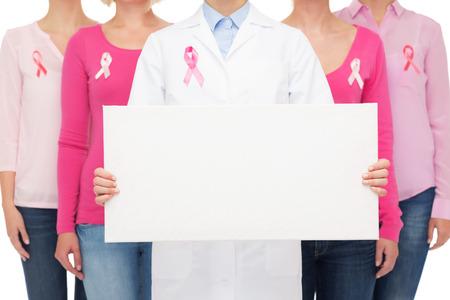 gezondheidszorg, mensen en geneeskunde concept - close-up van lachende vrouwen in shirts met roze borstkanker bewustzijn linten en leeg wit bord op witte achtergrond Stockfoto