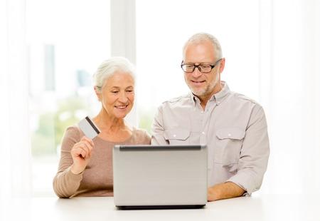 家族や技術、年齢の人々 の概念 - ラップトップ コンピューターや自宅でのクレジット カードと幸せな先輩カップル