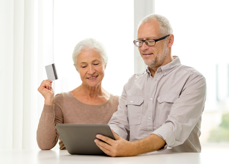 family, technology, age and people concept - happy senior couple with tablet pc computer and credit card at home photo