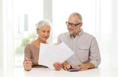 senior living: family, business, savings, age and people concept - smiling senior couple with papers and calculator at home Stock Photo