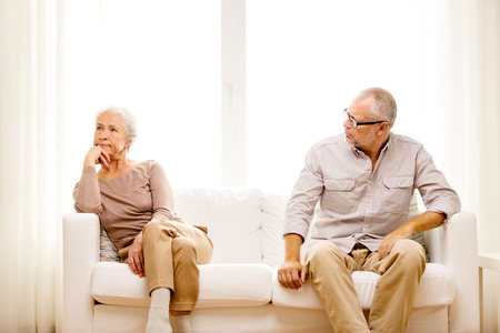 family, relations, age and people concept - senior couple sitting on sofa at home photo