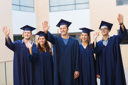 college building: education, graduation and people concept - group of smiling students in mortarboards and gowns waving hands outdoors