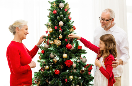 young tree: family, holidays, generation and people concept - smiling family decorating christmas tree at home
