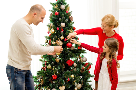 decorating christmas tree: family, holidays, generation and people concept - smiling family decorating christmas tree at home