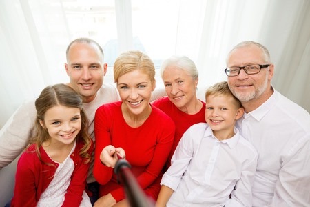 familiares, vacaciones, generación, Navidad y la gente concepto - sonriendo familia con cámara y palo Autofoto la toma de fotografías en casa