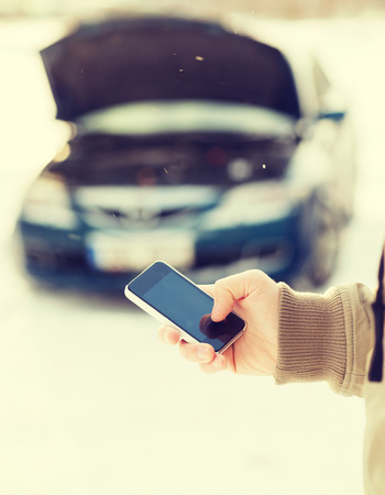 waiting phone call: transportation, winter and vehicle concept - closeup of man with broken car and cell phone