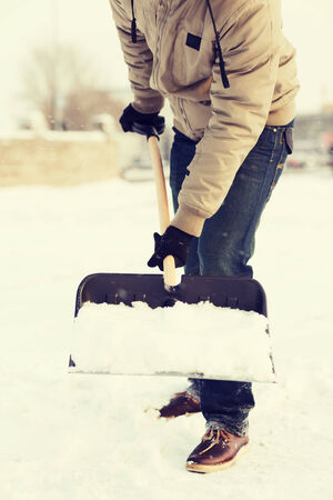 winter and cleaning concept - closeup of man shoveling snow from driveway photo